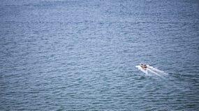 Ein einsames Boot, das heraus in den offenen Ozean schwimmt Lizenzfreie Stockfotos
