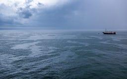 Ein einsames Boot während eines stürmischen Sonnenaufgangs, bunte Wolken Lizenzfreie Stockbilder