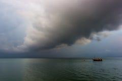 Ein einsames Boot während eines stürmischen Sonnenaufgangs, bunte Wolken Stockbild