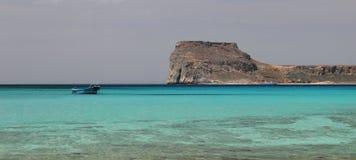 Ein einsames Fischerboot auf dem Smaragd bewegt in eine flache tropische Bucht, warmer Ozean wellenartig Stockbild