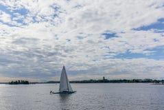 Ein einsames Segelboot mit den Skylinen von Helsinki im backgr stockfotos