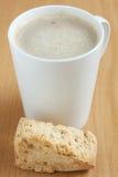 Ein einzelner Zwieback mit einem Becher Kaffee Stockbilder