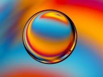 Ein einzelnes Öltröpfchen im Wasser mit buntem Hintergrund Stockfotografie
