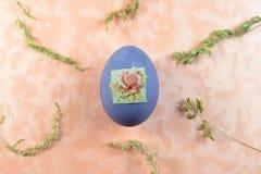 Ein einzelnes purpurrotes Ei liegt auf einem Rosenhintergrund stockbild