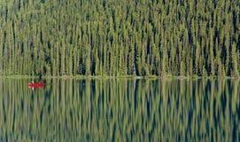 Ein einzelnes rotes Kanu schwimmt auf ein glasiges Lake Louise Stockbilder