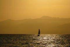 Ein einzelnes Segelbootsegeln im Ozean bei Sonnenuntergang Lizenzfreie Stockfotos