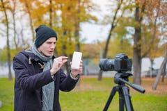 Ein einziger Kerl wird auf einer Kamera auf einem Stativ fotografiert, der einen Handy hält und seinen Fingern die Größe zeigt stockfotos
