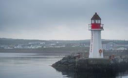 Ein einziger Leuchtturm auf einem Outcropping des Felsens in der Bucht von großartiger Bank, Neufundland, auf einem grauen Himmel Stockfoto