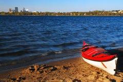 Ein einziger roter Kajak erwartet einen Reiter auf See Calhoun in Minneapolis lizenzfreies stockbild