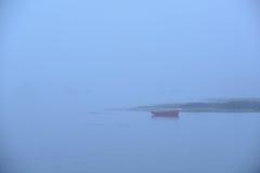 Ein einziges rotes Ruderboot oder ein Skiff im dichten Nebel Lizenzfreie Stockbilder