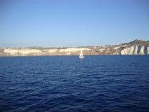 Ein einziges Segelboot vor der Küste der griechischen Insel von Santorini Lizenzfreie Stockfotografie