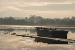 Ein einziges unbemanntes Boot sitzt Leerlauf auf einem gefrorenen See während des Sonnenaufgangs auf bloßem Hornsea lizenzfreie stockfotografie