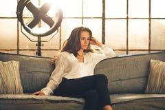 Ein eleganter Brunette sitzt auf einem Sofa stockfotografie