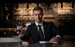 Ein eleganter, ernster und starker Geschäftsmann, der ein Glas des Kognaks hält und Kamera betrachtet Stockbilder
