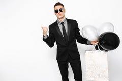 Ein eleganter Mann in einem schwarzen Anzug, mit Taschen in seinen Händen und Ball stockfoto