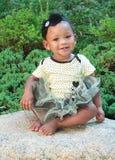 Ein elf Monats-altes Mädchen auf einem Felsen stockfotografie