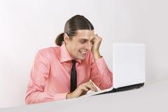 Ein emotionaler junger Mann mit Laptop stockbilder