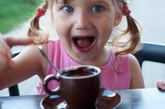 Ein emotionales Porträt eines lächelnden kleinen Mädchens mit einer Schale heißer Schokolade Lizenzfreies Stockbild