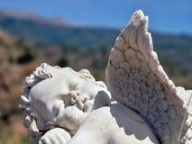 Ein Engel, der im Garten zwischen Blumen mit frontalview sitzt lizenzfreies stockbild
