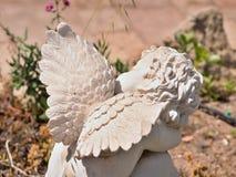 Ein Engel, der im Garten zwischen Blumen sitzt stockbild