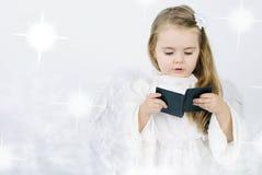Ein Engel des kleinen Mädchens mit einem Buch Lizenzfreie Stockfotografie