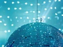Ein enormer hängender und spinnender Discoball reflektiert helle Blitze auf einer hellen Wand und schafft eine entspannte Stimmun Lizenzfreie Stockfotos
