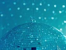 Ein enormer hängender und spinnender Discoball reflektiert helle Blitze auf einer hellen Wand und schafft eine entspannte Stimmun Lizenzfreies Stockfoto