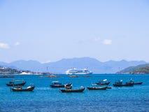 Ein enormes Kreuzschiff und eine Gruppe hölzerne Fischenschiffe Lizenzfreies Stockfoto