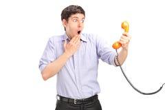 Ein entsetzter Mann, der ein Telefongefäß anhält Stockbild