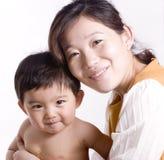 Ein entzückendes asiatisches Schätzchen und seine Mama Stockbild