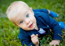 Ein entzückendes Baby auf dem grünen Gras Stockbilder