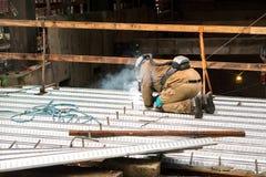 Ein erfahrener Bauarbeiterschweißer, der an einem Baueinsatzort arbeitet Lizenzfreies Stockfoto