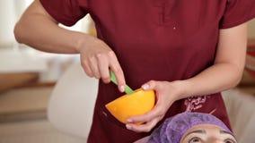 Ein erfahrener Cosmetologist bereitet eine gesunde Maske für den Kunden vor Sie steht auf und berührt das Gesicht mit einer Bürst stock footage