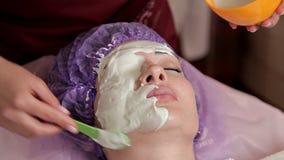 Ein erfahrener Cosmetologist bereitet eine gesunde Maske f?r den Kunden vor Sie steht auf und ber?hrt das Gesicht mit einer B?rst stock footage