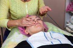 Ein erfahrener Cosmetologist wendet eine Maske der Emulsion auf dem Gesicht eines jungen Mädchens an, das auf der Couch während d stockfotografie