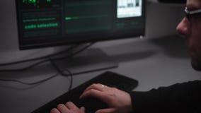 Ein erfahrener Hacker schafft ein Programm für das Zerhacken des Bankservers Auf dem Schirm wird vielem Computer analysiert stock footage
