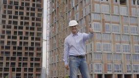 Ein erfolgreicher Erbaueringenieur in einem weißen Sturzhelm 4K stock video