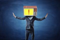 Ein erfolgreicher Geschäftsmann hebt seine Hände zu seinem Kopf an, der durch ein altes Fernsehen ersetzt wird, das ein rotes Aus Lizenzfreie Stockfotos