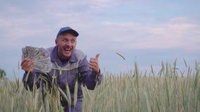 Ein erfolgreicher glücklicher junger Landwirt hat viel Geld Das Konzept des Erfolgs des Geschäfts in der Landwirtschaft stock footage