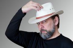 Ein ernster b?rtiger Mann von mittlerem Alter setzt an einen Cowboyhut lizenzfreie stockfotografie