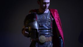 Ein ernster Gladiator steht in der ledernen Rüstung und ein Regenmantel und in seiner Hand hält einen Metallsturzhelm und untersu stock video footage