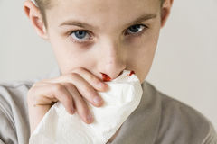 Ein ernster Junge benutzt Gewebe, um Nase, zu bluten aufzuhören Lizenzfreie Stockfotos