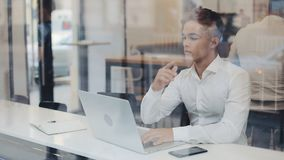 Ein ernster junger Geschäftsmann, der an einem Tisch in einem Café arbeitet auf einem Laptop sitzt , Sind Kommunikation, IT freib stock video