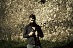 Ein ernster Mann 13 Steinige Wand und Mann mit Axt Stockbild
