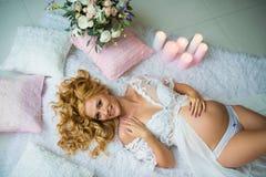 Ein erstaunlich schönes rothaariges schwangeres Mädchen mit frischen Blumen stockfotografie
