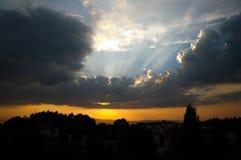 Ein erstaunlicher Sonnenuntergang mit dem Sonnenlicht, das über Wolken nachdenkt stockfoto