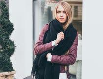 Ein erstaunliches langhaariges blondes Mädchen, das in der modernen Kleidung, eine Jacke, schwarze Jeans am Eingang zum Restauran Stockfotografie