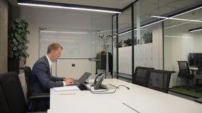 Ein erwachsener Geschäftsmann, der allein an seinem Schreibtisch mit Laptop im Büro arbeitet stock video footage