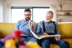 Ein erwachsener Hippie-Sohn und ein älterer Vater, die zuhause auf Sofa zu Hause sitzen stockbild