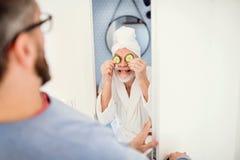 Ein erwachsener Hippie-Sohn und ein älterer Vater im Badezimmer zuhause zu Hause, Spaß habend stockfotografie